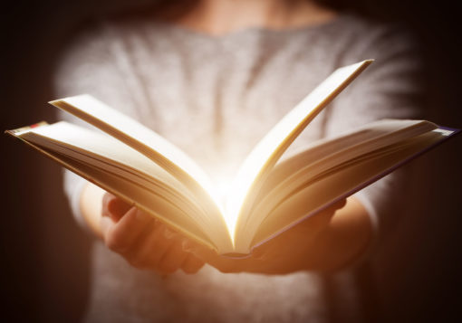 50832678 - light coming from book in woman's hands in gesture of giving, offering. concept of wisdom, religion, reading, imagination.